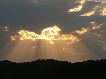雲の隙間から夕陽の光が差して…